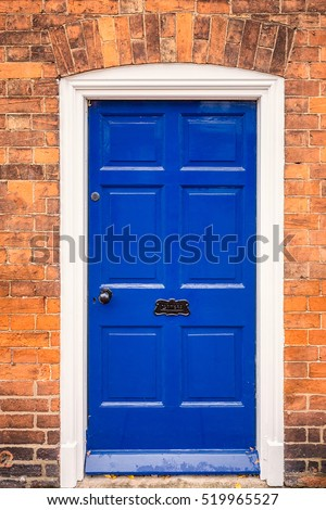 Blue door with brick wall at England, UK.