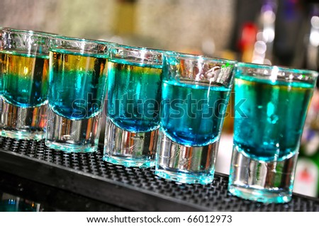 Blue drink in shot glasses standing on the counter