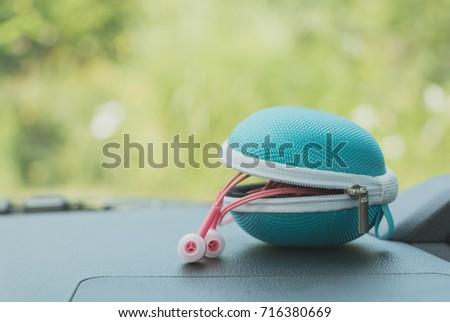 blue earphone case and pink earphone on dashboard car