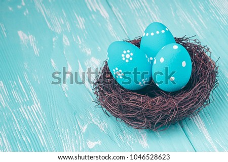 Blue Easter eggs in nest on blue wooden background. #1046528623