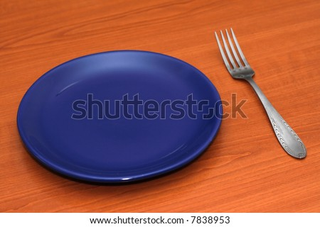 Blue empty plate and a fork on a table