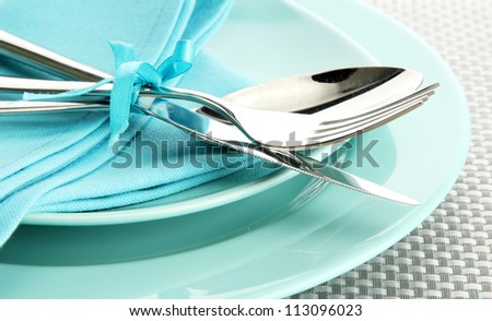 blue empty plates with fork, spoon and knife on a grey tablecloth