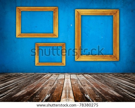 blue empty room with wooden floor and empty frame hanging on the wall - stock photo