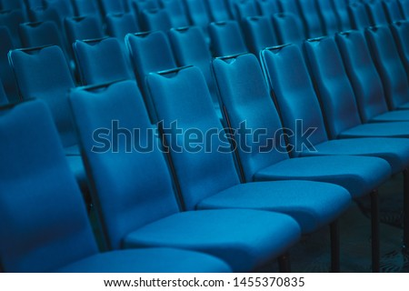 Blue empty seats in the audience prepared for the participants of the conference or presentation. Organization and holding of mass events. Soft classical empty chairs in a row chairs.