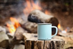Blue enamel cup of hot steaming coffee sitting on an old log by an outdoor campfire. Selective focus on mug with blurred background.