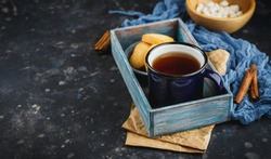 Blue enamelled cup of tea, cinnamon sticks, anise stars and shortbread on a dark background. Space for text.