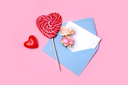 Blue envelope for a letter with pink flowers and a heart-shaped candy cane. Valentine's Day concept. Flat lay style