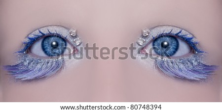 Blue eye macro closeup with a winter inspired silver makeup some jewels and feather eyelashes
