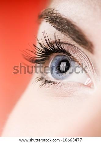 Blue eye on red background (shallow DoF)