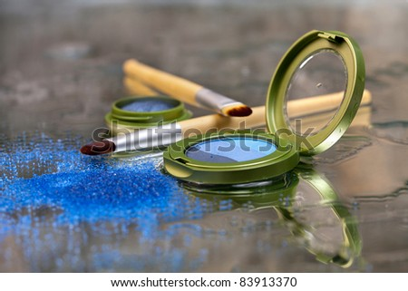 Blue eye shadow / Blue eye shadows and makeup brushes placed on a wet mirror