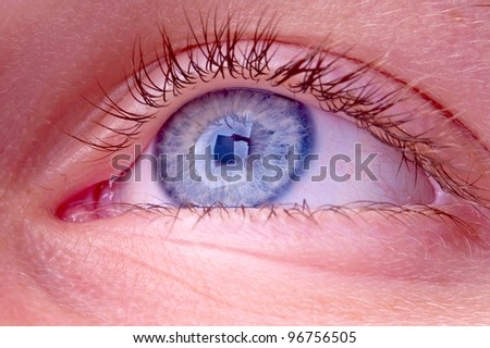 blue eye with reflection of a person holding a sign