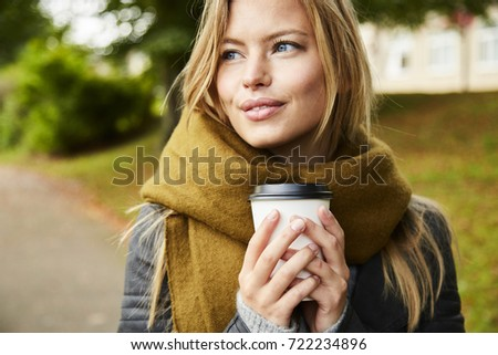 Blue eyed blond woman with coffee in park, looking away Stock photo ©