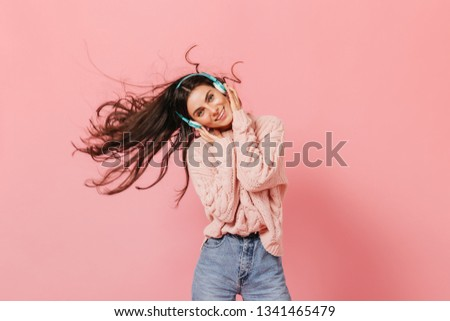 Blue-eyed girl with snow-white smile is listening to song in turquoise-colored headphones. Woman in knitted pullover dancing on pink background #1341465479