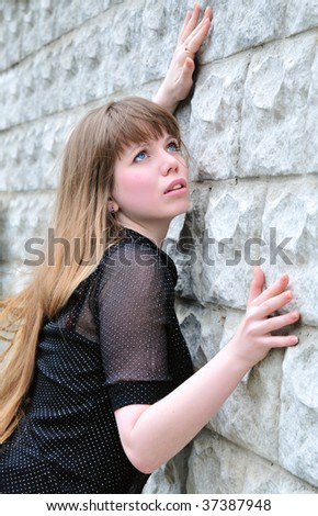 Blue-eyed long-haired girl leans on elbow wall and looks up