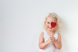 Blue eyed pretty small kid dressed casually, has fun indoors, covers eye with heart stick, glad to spend free time with her parents, isolated over white background with copy space for your text