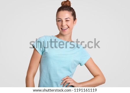 Blue eyed satisfied attractive girl blinks at camera, keeps one hand on waist, has hair bun, dressed in blue casual t shirt, poses against white background, flirts with man. Hey, guy come here.