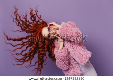 Blue-eyed woman in lilac glasses dances and plays with her hair. Picture of girl in pink coat on isolated background