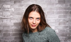 Blue-eyed woman on a background of a brick wall