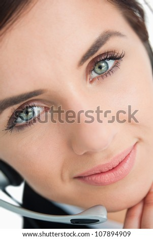Blue eyed woman with headset in close-up - stock photo