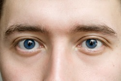 blue eyes of a man close up. the concept of ophthalmology optics and medicine. the male gaze