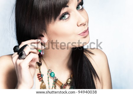 blue eyes woman put on earring, studio shot