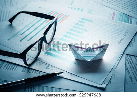 Blue filter effects images.Glasses and pen with boats made of paper graph on business document paper.Business Analysis concept. #525947668