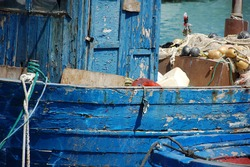 blue fishermen's boat side with a fishermen's net and marine equipment inside docked in a mediterranean port. Working at sea.
