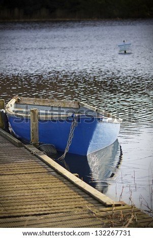 Blue fishing boat moored on a small, semi-frozen loch