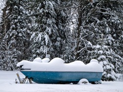 Blue Fishing Boat on trailer is covered with snow, as are the branches of the nearby trees in this Minnesota winter scene.