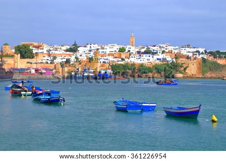 Blue fishing boats on the Bou Regreg river and distant Kasbah of the Udayas in Rabat, Morocco