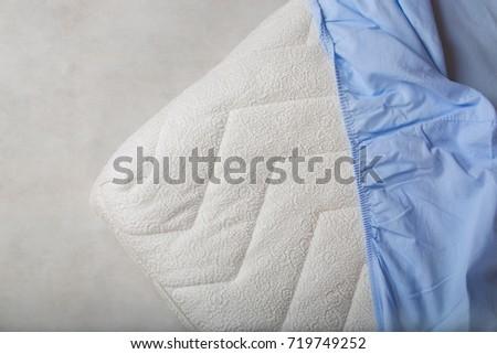 Blue fitted sheet on a mattress. Top view. Closeup