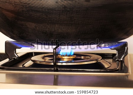 Blue Flame of a Gas Cooker heating a Wok