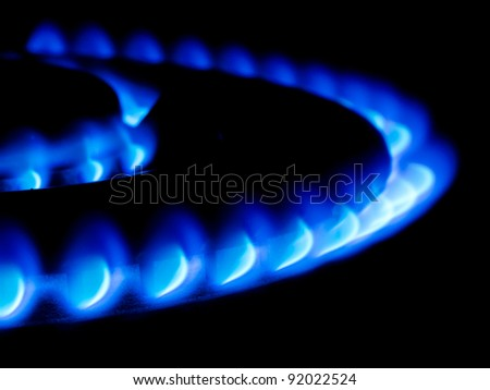 blue flames from a double ring giant gas stove in the dark