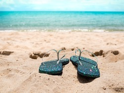 Blue flipflop on sand beach at coast with blue sea and blue sky blured.accessories for travel summer holidays concept.