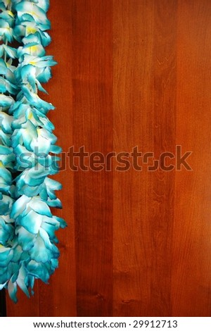 Blue floral hawaiian lei isolated on wooden background