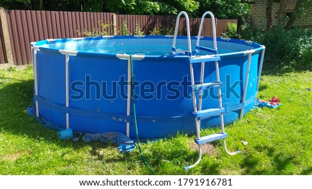 Blue frame swimming pool on the green lawn near the house Foto stock ©