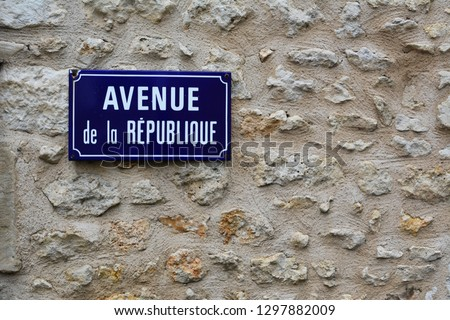 Blue french street sign in french with the writing in english