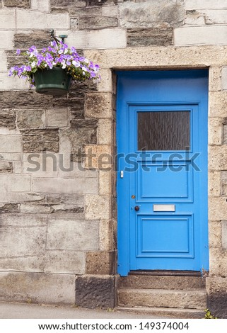 Blue front door in a English stone wall house with hanging flower basket.