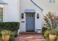 Blue front door of traditional style home with brick entry and white brick exterior.