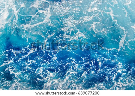 Blue frothy surface of sea water, shot in the open sea directly from above