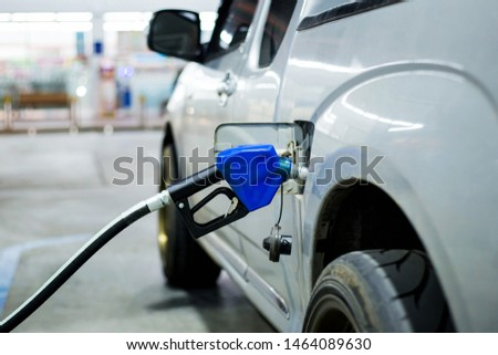Blue fuel nozzle fueling a car in gasoline stations. #1464089630