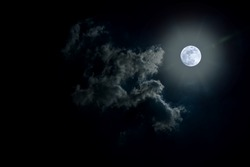 Blue full moon on cloudy day.
