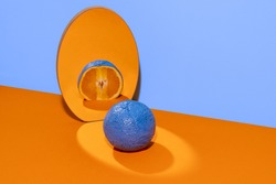Blue full orange on a mirror with half reflection. Blue and orange background