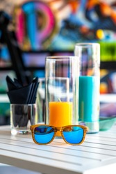 Blue funky sunglasses on white table with black napkins, orange juice setup and funky Graffiti background