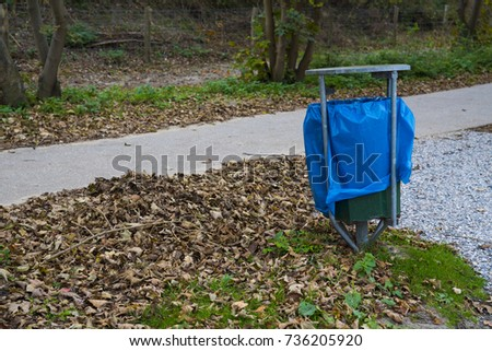 blue garbage bag in green iron bucket, in park along hiking path