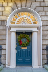 Blue Georgian door, decorated for Christmas with green wreath and red decorations. Dublin, Ireland. Timber entrance with stone columns and decorative arch window fanlight