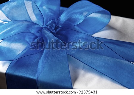 Blue gift bow on silver, close-up