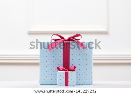 blue gift box on white table. Different sizes of the same shape gift box. A small gift box with a big gift box.