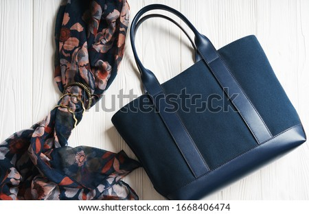Blue girl hand bag and scarf with golden accessories on wooden white surface ストックフォト ©