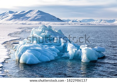 Blue glacial iceberg at the edge of the fast ice, Nordfjorden fjord. Svalbard,. Сток-фото ©
